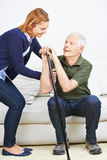 Woman helping senior man getting up Royalty Free Stock Images