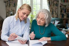 Woman Helping Senior Neighbor With Paperwork. Woman Helps Senior Neighbor With Paperwork Royalty Free Stock Images