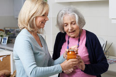 Woman Helping Senior Neighbor To Remove Jar Lid Royalty Free Stock Photography