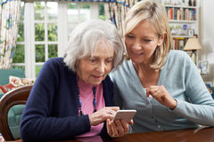 Woman Helping Senior Neighbor To Use Mobile Phone Stock Photography