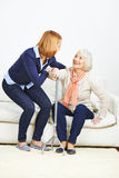 Woman helping senior woman getting up Royalty Free Stock Photos