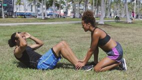 Woman helping to boyfriend with abdominal exercise stock video footage
