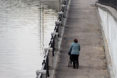 Woman helping to roll a wheelchair with a person along the promenade stock images