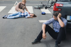 Woman helping an unconscious victim. While shocked driver sitting next to his car Stock Photography