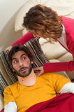 Woman Helping Victim in Neck Brace Get Comfortable. A woman is assisting an injured man in a neck brace by repositioning his pillow for him stock image