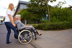 Woman helping wheelchair user. Young woman helping elderly woman in wheelchair over a curbstone Stock Images