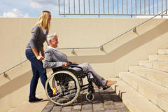 Woman helping wheelchair user. Young woman helping an elderly woman in wheelchair with staircase Stock Photography