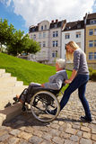 Woman helping wheelchair user. Young woman helping an elderly woman in wheelchair Royalty Free Stock Images