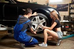 Woman helps an auto mechanic repair front wheel of car Stock Photography