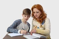 Woman helps boy to do homework Stock Photo
