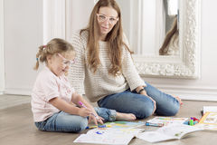 Woman helps a child to draw. Mother helps daughter to draw with markers Royalty Free Stock Image