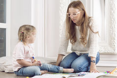 Woman helps a child to draw. Mother helps daughter to draw with markers Royalty Free Stock Photography