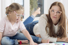 Woman helps a child to draw. Stock Photos