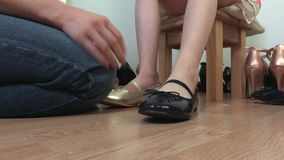 Woman helps a child try on shoes stock video