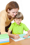 A woman helps first graders how to write in a notebook Stock Images