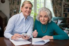 Portrait Of Woman Helping Senior Neighbor With Paperwork. Woman Helps Senior Neighbor With Paperwork Stock Image