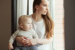 Woman and her adorable baby child looking in window. Waiting for father. Happy mother and son watching far away, mother and toddler together stock image