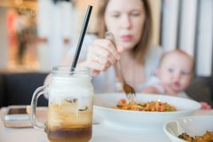 Woman and her baby boy in a cafe. Eating lunch spaghetti and having cold coffee stock image