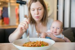 Woman and her baby boy in a cafe. Eating lunch spaghetti royalty free stock image
