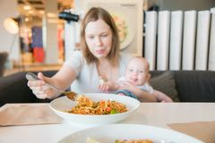 Woman and her baby boy in a cafe. Eating lunch spaghetti stock photography