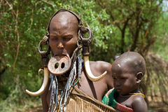 Woman with her baby of the Mursi tribe. OMO VALLEY, ETHIOPIA - MARCH 13, 2010: An unidentified woman of the Mursi tribe with traditional ornaments and lip plate Royalty Free Stock Photo