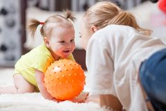 Woman with her baby playing with a ball, while they are lying on plush carpet in the living room Royalty Free Stock Photography