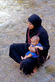 Woman with her baby in the river of The Todra gorges in Morocco stock photo