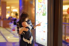 Woman with her baby in a shopping mall Stock Photos