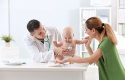 Woman with her baby visiting children`s doctor. In hospital stock photo