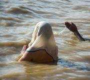 Woman on her back bathing and praying in the Ganges river, in Varanasi, India stock photo
