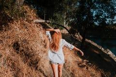 Woman walking along narrow path in nature. Stock Image