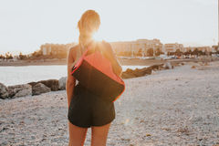 Woman on her backs standing with a sports bag on the shoulder. Stock Photo
