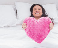 Woman in her bed holding a fluffy heart cushion Royalty Free Stock Images