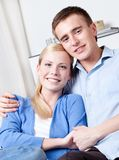 Woman and her boyfriend hug each other on the sofa Stock Image
