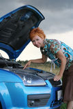 Woman with her broken car. Young red-haired woman with her broken car. The girl have a big problem Royalty Free Stock Photos