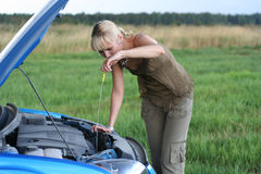 Woman with her broken car. Young blond woman with her broken car. The girl is sad Royalty Free Stock Image