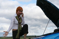 Woman with her broken car. Young red-haired woman with her broken car with mobile phone. The girl have a big problem Stock Photo