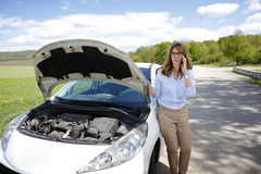 Woman with her broken down car Stock Images
