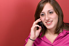 Woman On Her Cell Phone. A young business woman talking on her cell phone isolated over a red background Stock Photo