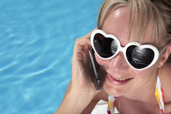 Woman on her Cellphone by the Pool Royalty Free Stock Photography