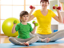 Woman and her child daughter doing fitness exercises with dumbbells Stock Photos