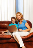 Woman and her child with laptop on the couch Royalty Free Stock Images