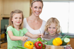 Woman with her children preparing salad Stock Images