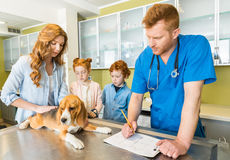 Woman and her children with their dog at veterinary doctor. In clinic Royalty Free Stock Images