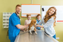 Woman and her children with their dog at veterinary doctor Stock Photo