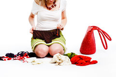Woman and her clothes. Young woman and her clothes - after shopping, looking at new pants Royalty Free Stock Photo