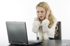 Woman at her computer, shocked about what is on the screen Royalty Free Stock Images