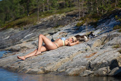 Woman with her cute dog is laying on the stone beach near of the White sea Stock Photography