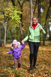 Woman  with her daughter in the autumn park Stock Images