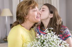 Woman and her daughter with a bouquet of flowers in their house. royalty free stock images